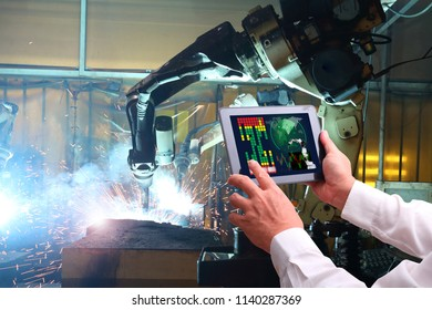Engineer hand using tablet with machine real time monitoring system software.digital manufacturing operation. Automation robot arm machine in smart factory automotive industrial , Industry 4.0 concept
