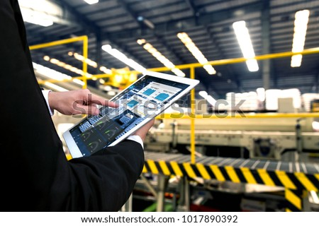 Engineer hand using tablet with machine real time monitoring system software. Automation robot arm , conveyor belt machine  in smart factory industry 4th iot , digital manufacture.