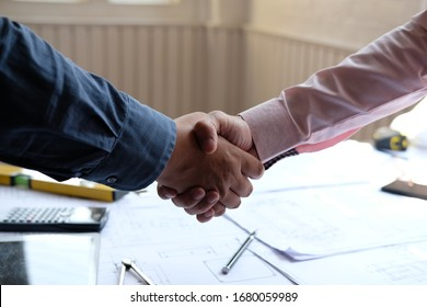 engineer handshaking. architect shaking hands for successful deal in building construction project. teamwork cooperation concept