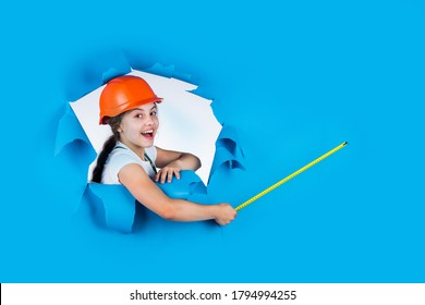 engineer. happy child hold tape measure. kid builder wear helmet. teen girl in hard hat and uniform. building and construction. concept of repair. Little girl using a measuring tape. copy space.