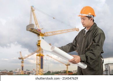 Engineer with hard hat reading blueprint at construction site.