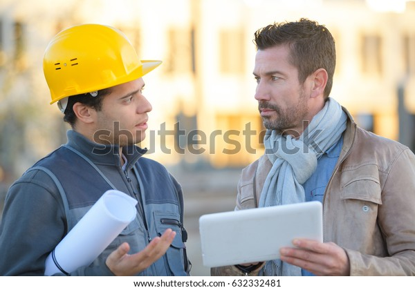 engineer with hard hat using tablet talking to supervisor