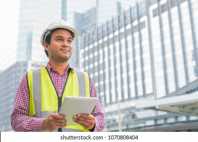 Engineer with hardhat is holding a tablet computer looking forward on building background. Construction manager concept.