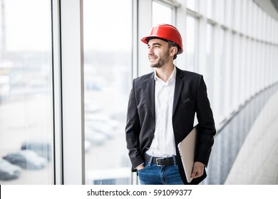 Engineer in hardhat with laptop computer, smiling at camera.