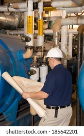 Engineer with hardhat looking on blueprint in power plant