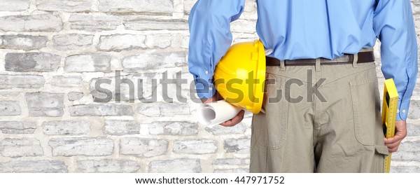 Engineer with helmet and blueprint.