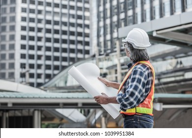engineer in helmet holding blueprint,Worker in a construction site,Business engineer planing at construction site