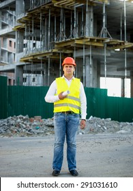 Engineer in helmet on construction site posing against scaffolding