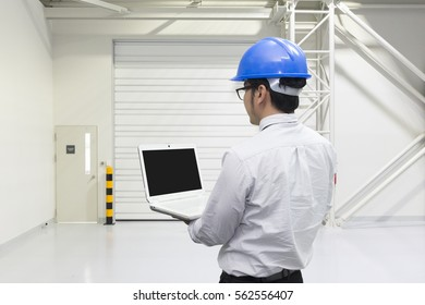 The  engineer hold the laptop by the hand at the inside of the factory
