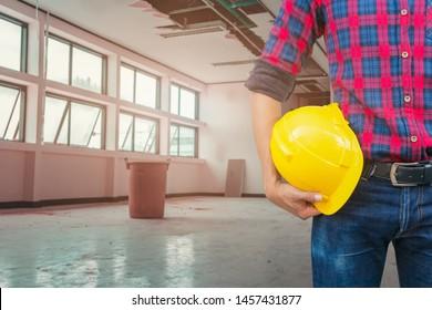 Engineer hold safety helmet inspect in repair leak water pipe under gypsum ceiling interior office building and bucket water background