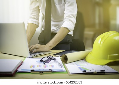 engineer hold security helmet and blueprint paper construction drawing plan near laptop computer,Architect working in office,Engineering tools on desk at site project