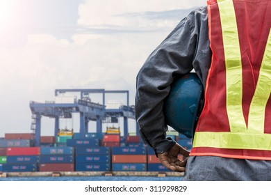 Engineer holding a blue helmet for the safety of workers on the background  port with cranes and containers