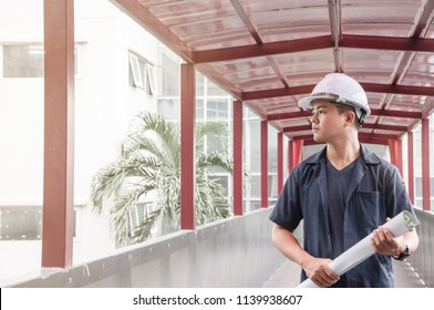 Engineer holding a blueprint for his work at link way, Engineering student wear safety helmet, Asian engineer walking on link way, Portrait of young engineer holding blueprint walking on bridge