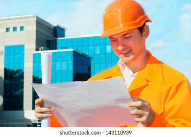 Engineer holding a blueprints with a business center at the background