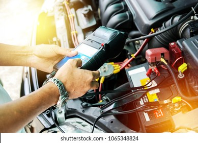 Engineer holding Handheld device for Check up car battery life.