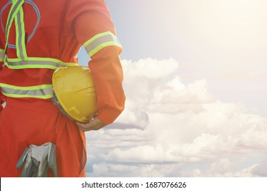 Engineer holding hard helmet with cloud and blue sky background,safety first concept