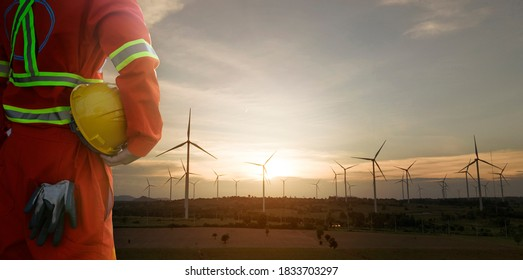 Engineer holding helmet with wind turbines plant for electric power production silhouette at sunset ,clean energy concept