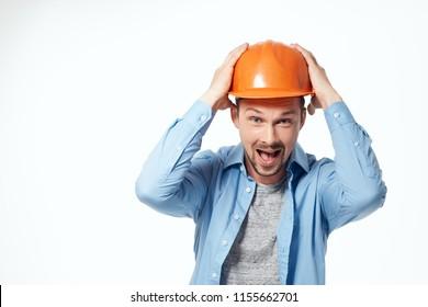 the engineer is holding his helmet on his head