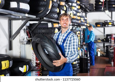 engineer holding new tyre for motorcycle in tire shop