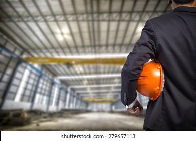 engineer holding orange helmet for workers security on factory background  apartm