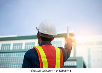 Engineer holding paper plan against building sky background