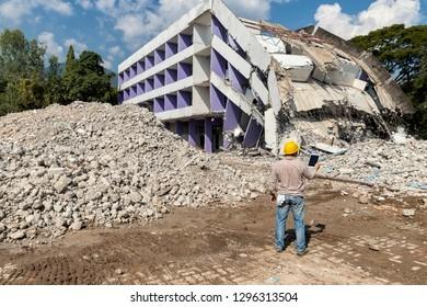 Engineer holding tablet is checking for destruction, demolishing building.