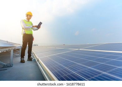 The engineer holding a tablet is checking the solar panel on the roof of the building to save energy. Using solar cells is energy saving. Renewable energy concepts.