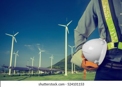 Engineer holding a white helmet. Against a backdrop of renewable energy farms. Vintage Style.