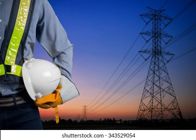 Engineer holding a white helmet for the safety of workers on the background. Silhouette transmission towers on the background of the evening sun.