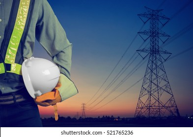 Engineer holding a white helmet for the safety of workers on the background. Silhouette transmission towers on the background of the evening sun. Vintage Style
