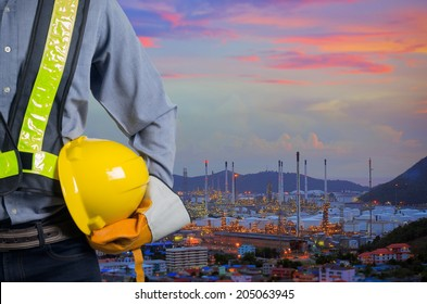 Engineer holding a yellow helmet for the safety of workers on the background oil refinery. Beautiful sky at dawn