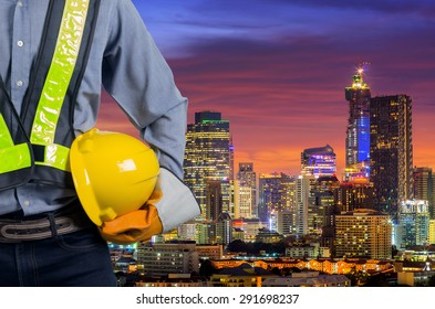 Engineer holding a yellow helmet for safety of the workers. A modern high-rise structures in the background.