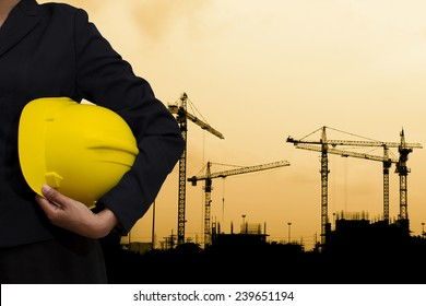 engineer holding Yellow helmet for workers security on background of building construction