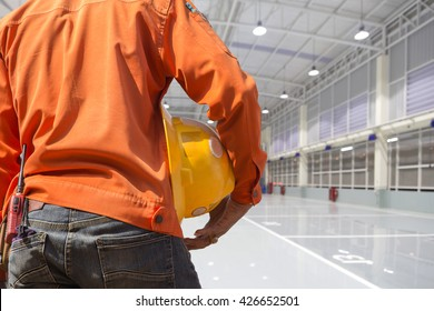 engineer holding yellow helmet for workers security on indoor factory epoxy floor construction site background
