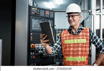 Engineer Industry holding tablet in hand of plan work with factory background , Engineer looking of working at industrial machinery setup in factory.