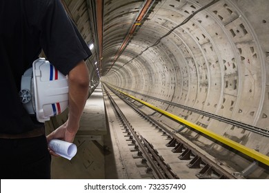 The engineer or inspector hold helmet and drawing in underground railway tunnel