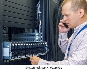 IT Engineer installs enclosure with hard disk drive in the storage system in the rack in data center