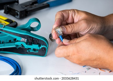 The engineer installs the new connector on the cable using a tool. Crimping tool for internet cable, cable and connectors on the engineer's desktop.
