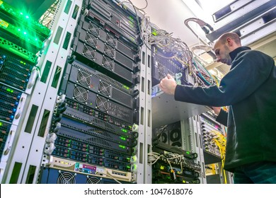 The engineer installs the new equipment in the server rack of the data center. The technical specialist works in the server room. Bottom view