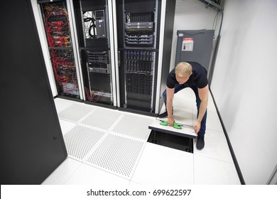 IT Engineer Lifting Floor Tile Using Suction Cups In Datacenter