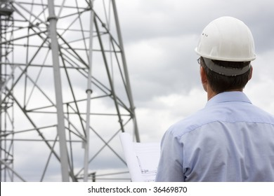 Engineer looking at construction side with plan in his hand