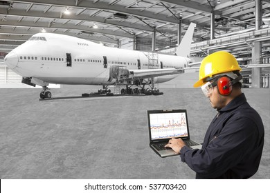 Engineer looking at laptop for maintenance an airplane are performing repairs, fixes, modernization and renovation in the aviation hangar