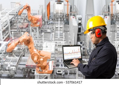 Engineer looking at laptop for programing computer controlling robot hands automation and conveyor belt in the factory