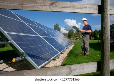 Engineer looking at plans standing next to large solar panels