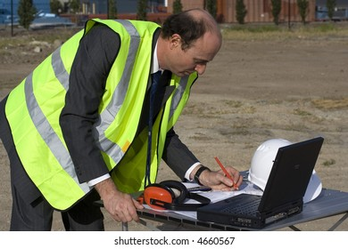 Engineer looking thoughtful, wearing high visibility yellow vest over his suit and on the table in front of him are his laptop, blueprints, ear muffs and white safety helmet