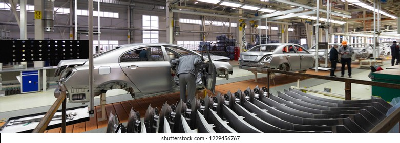 Engineer looks into the cab of the car on the production line. Automotive production line. long format. Wide frame