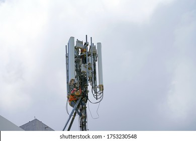 Engineer maintenance on telecommunication tower doing ordinary maintenance & control to an antenna for communication, 3G, 4G and 5G cellular. Cell Site Base Station on white clouds background. - Shutterstock ID 1753230548