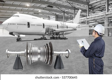 Engineer maintenance record an airplane are performing repairs, modernization and renovation in the aviation hangar