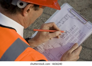 Engineer making adjustments to plan with a pencil, with the plans on a clipboard, with the well dressed engineer wearing high visibility clothing