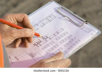 Engineer making changes to the blueprints on a clipboard with a pencil